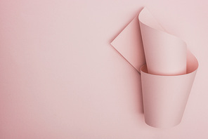 top view of pink paper swirl on pink background