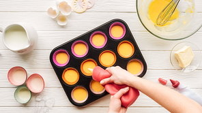 selective focus of cupcakes with kumquats on pink surface