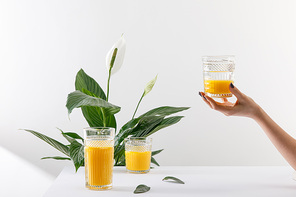 cropped view of woman holding glass of fresh delicious yellow smoothie near green peace lily plant on white