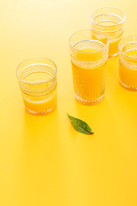 glasses of fresh delicious yellow smoothie near green leaf