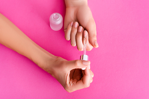 partial view of woman applying cuticle remover with dropper on pink background