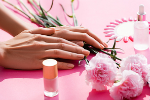 cropped view of female hands near carnation flowers, bottles of nail polish and cuticle remover, and fake nails palette on pink