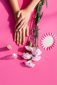 top view of female hands near carnation flowers, palette of artificial nails, cuticle remover and nail polish on pink background