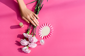 top view of female hands near bottles with nail varnish and cuticle remover, carnation flowers and palette of fake nails on pink background
