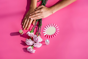 top view of female hands near palette of false nails, carnation flowers, and bottles of cuticle remover and enamel on pink background