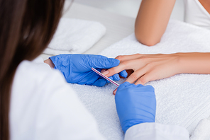 cropped view of manicurist making manicure for client with nail file, selective focus