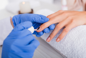 cropped view of manicurist applying nail varnish on fingernail of client, blurred foreground