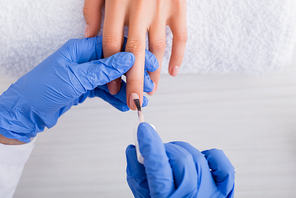 partial view of manicurist in latex gloves applying nail varnish while making manicure to client
