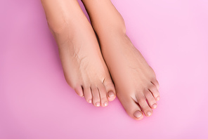 top view of groomed female feet with glossy toenails on pink background