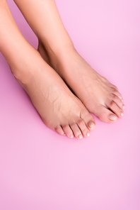 top view of groomed female feet with pastel nail varnish on toenails on pink background