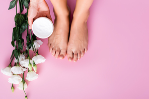 cropped view of woman holding cosmetic cream near groomed feet and white eustoma flowers on pink background