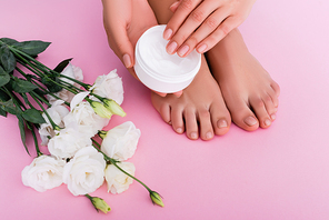 partial view of barefoot woman holding cosmetic cream near white eustoma flowers on pink background