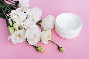 white eustoma flowers and cosmetic cream on pink background