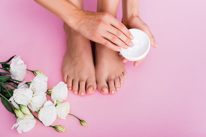 cropped view of barefoot woman holding cosmetic cream near white eustoma flowers on pink background