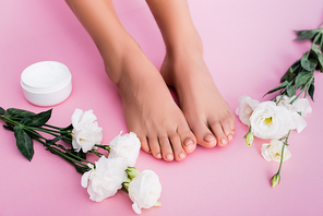 top view of eustoma flowers near cosmetic cream and female legs with pastel pedicure on pink background