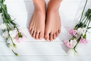 top view of female feet with pastel pink toenails near carnation and eustoma flowers on white wooden surface