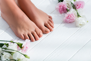 female feet with pastel pink toenails near carnation and eustoma flowers on white wooden surface