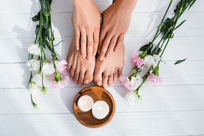 top view of female feet and hands with pastel pink enamel on nails near flowers and candles on white wooden surface