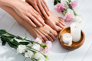 female feet and hands with glossy pink nails near carnation and eustoma flowers and candles on white wooden surface
