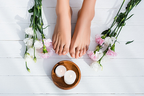 top view of groomed female feet, bowl with candles, eustoma and carnation flowers on white wooden surface
