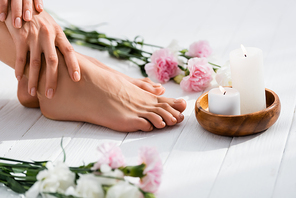 cropped view of woman with groomed hands and feet near candles and flowers on white wooden surface, blurred foreground