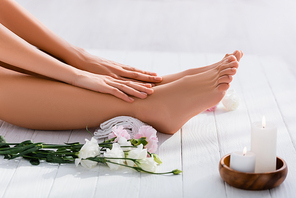 cropped view of woman with groomed hands and feet near white eustoma flowers and candles on white wooden surface