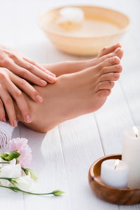 groomed female hands and feet with pastel pink nails on white wooden surface near eustoma flowers and candles on blurred foreground