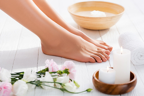 groomed female feet near eustoma flowers, candles and rolled towel on white wooden surface