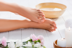 groomed female feet near bowl on wooden surface near eustoma flowers and candles on blurred foreground