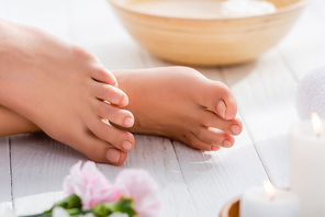cropped view of female feet with pink pastel pedicure on white wooden surface, blurred foreground