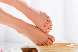 groomed female feet with glossy pink toenails near wooden bowl on white