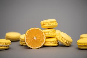 delicious yellow macarons near half of juicy lemon on grey background