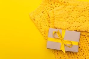 top view of wrapped present near knitted jumper isolated on yellow