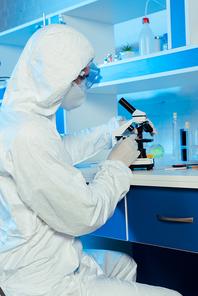 scientist in hazmat suit and goggles near microscope in laboratory