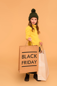 girl in brown hat and yellow turtleneck holding shopping bag with black friday lettering on beige