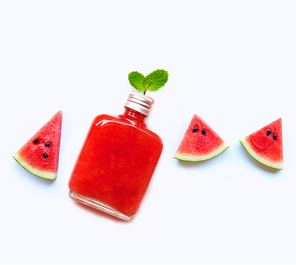 Bottle of healthy watermelon juice with slice and mint leaves isolated on white background.