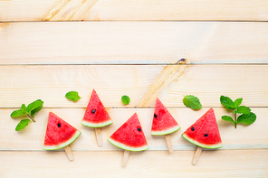 Watermelon slice popsicles on brown wooden background. Top view