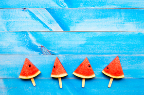 Watermelon slice popsicles on blue wooden background. Top view