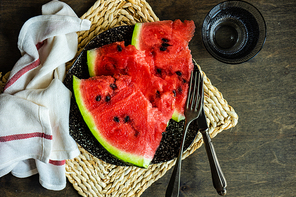 Ripe organic watermelon slices on a plate as a summer dessert on wooden table