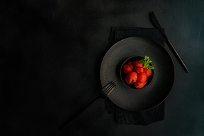Served summer dessert with watermelon balls and mint in black stoneware on black background