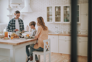 Smiling man holding a plate with pancakes while his son and wife sitting in front of him at the kitchen table