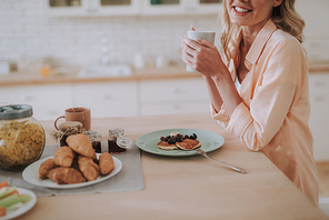 Cheerful smiling woman holding a cup of tea while sitting at the kitchen table with plate of pancakes in front of her