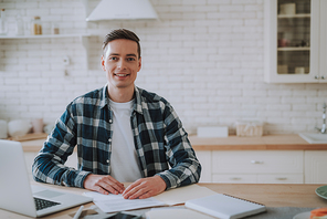 Positive handsome young man putting hands on the table and smiling while sitting in the kitchen with a modern laptop and documents