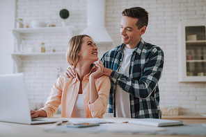 Caring young man smiling to his wife while massaging her shoulders in the kitchen