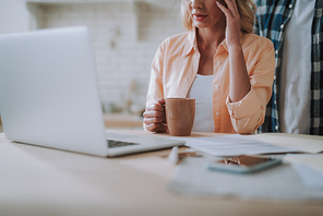 Young tired woman sitting with a cup of tea in front of modern laptop and touching her head