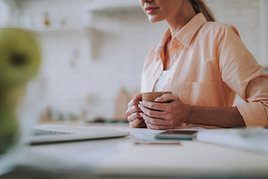 Young woman sitting at the table in front of the laptop with a cup of tea. Copy space on the left side