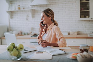Young relaxed woman sitting in the kitchen with a cup of tea and smiling while talking on the phone and looking into the distance