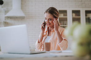 Young woman feeling glad while sitting in the kitchen in front of the laptop and having a pleasant phone talk