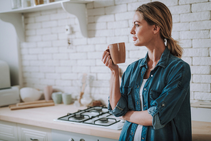 Calm young woman in casual clothes standing with a cup of tea in her hands and thoughtfully looking away. Copy space on the left side
