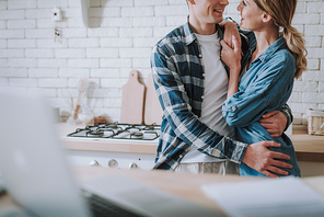 Romantic atmosphere. Young man and woman in casual clothes standing in the kitchen and smiling to each other while hugging. Copy space on the left side